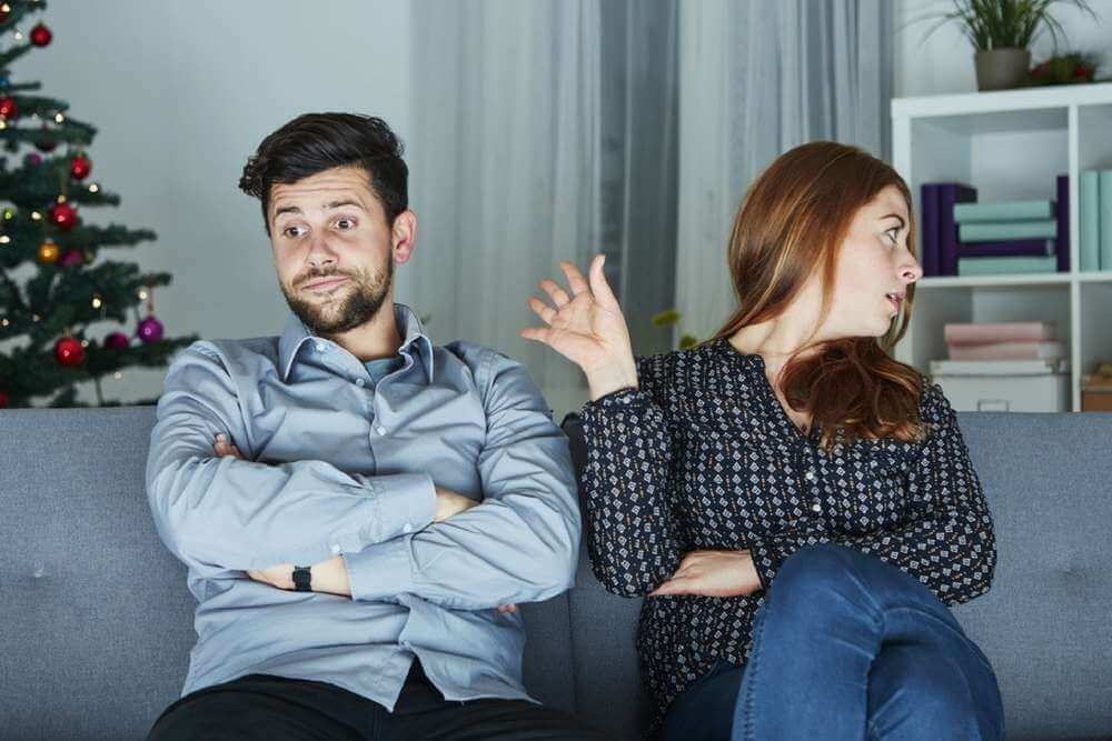 lighthousetreatment-how-to-manage-addiction-triggers-during-the-holidays-article-young-modern-couple-is-irritated-of-christmas-with-christmas-tree-in-background-335250644