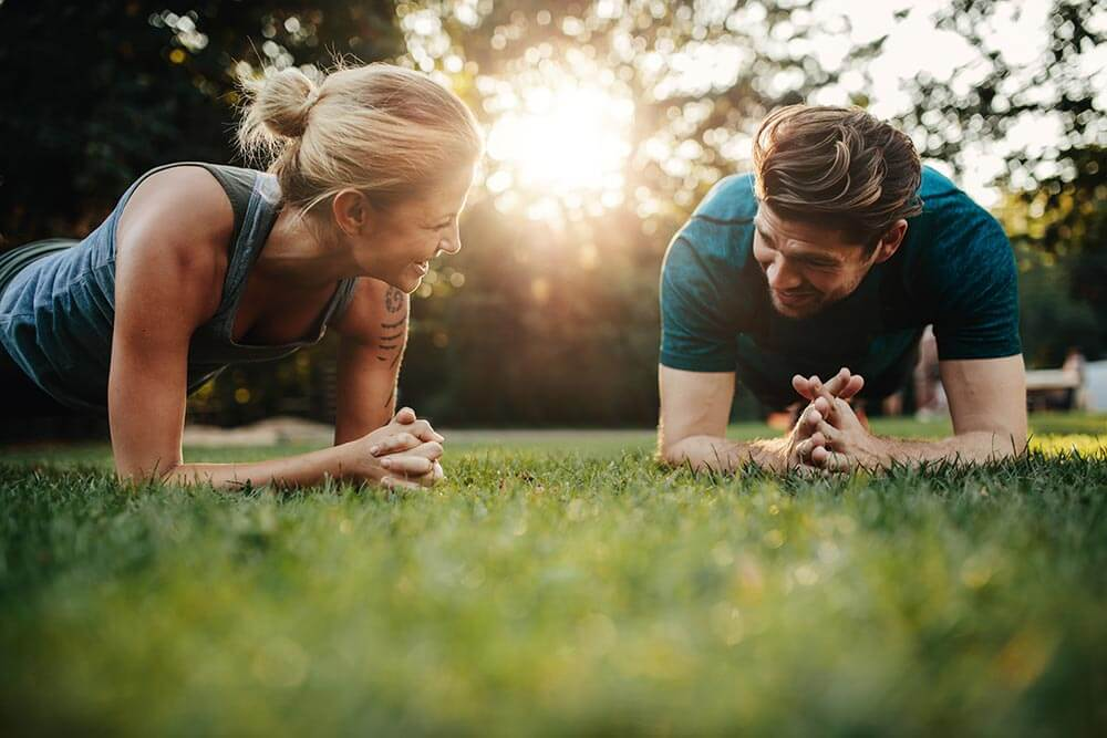 lighthousetreatment-7-ways-to-deal-with-anxiety-in-recovery-article-photo-of-fit-young-man-and-woman-exercising-in-park-smiling-caucasian-couple-doing-core-workout-on-grass-522539509