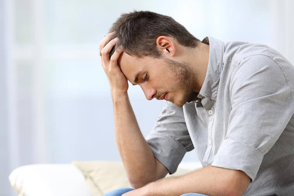 lighthousetreatment-7-ways-to-deal-with-anxiety-in-recovery-article-photo-of-side-view-of-a-sad-man-with-a-hand-on-the-head-sitting-on-a-couch-in-the-living-room-at-home-457511662
