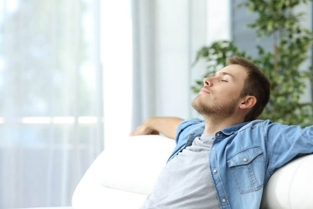 lighthousetreatment-how-mindfulness-affects-addiction-recovery-article-photo-of-portrait-of-a-casual-tired-man-resting-sitting-on-a-couch-at-home-446681404