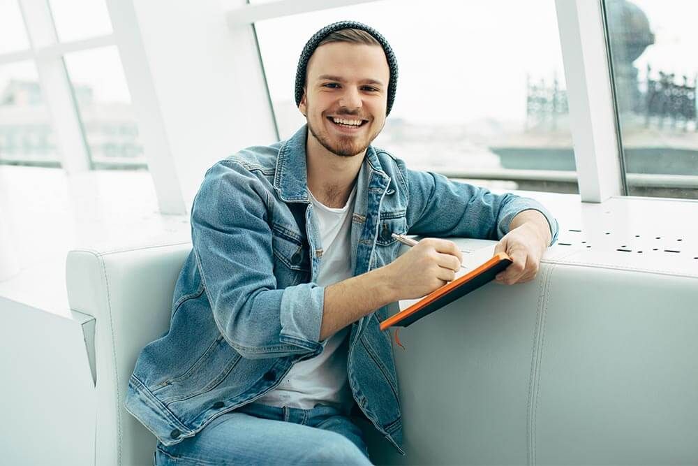lighthousetreatment-10-good-reasons-to-get-clean-and-sober-article-photo-smiling-man-is-sitting-on-sofa-and-writing-down-some-notes-he-is-happy-young-student-524721709