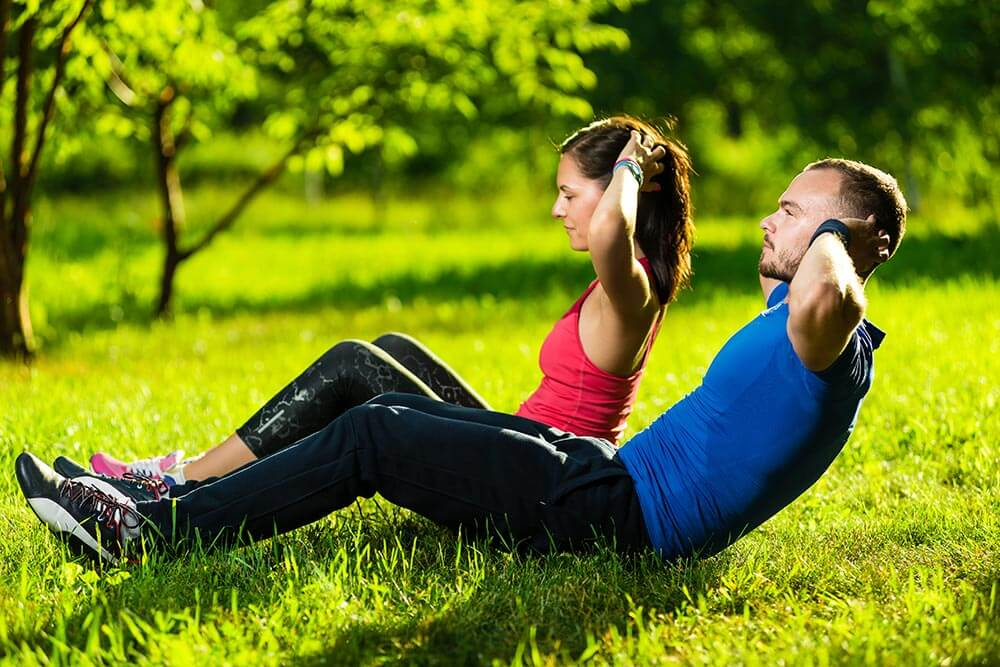 lighthousetreatmentstock-insomnia-in-recovery-non-pharmaceutical-options-article-photo-man-and-woman-exercising-at-the-city-park-beautiful-young-multiracial-couple-sit-ups-fitness-277279514