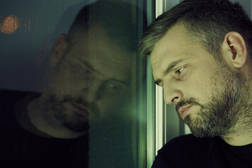 lighthousetreatment-have-i-hit-my-rock-bottom-article-photo-depressed-man-looking-sadly-through-the-window-569056993