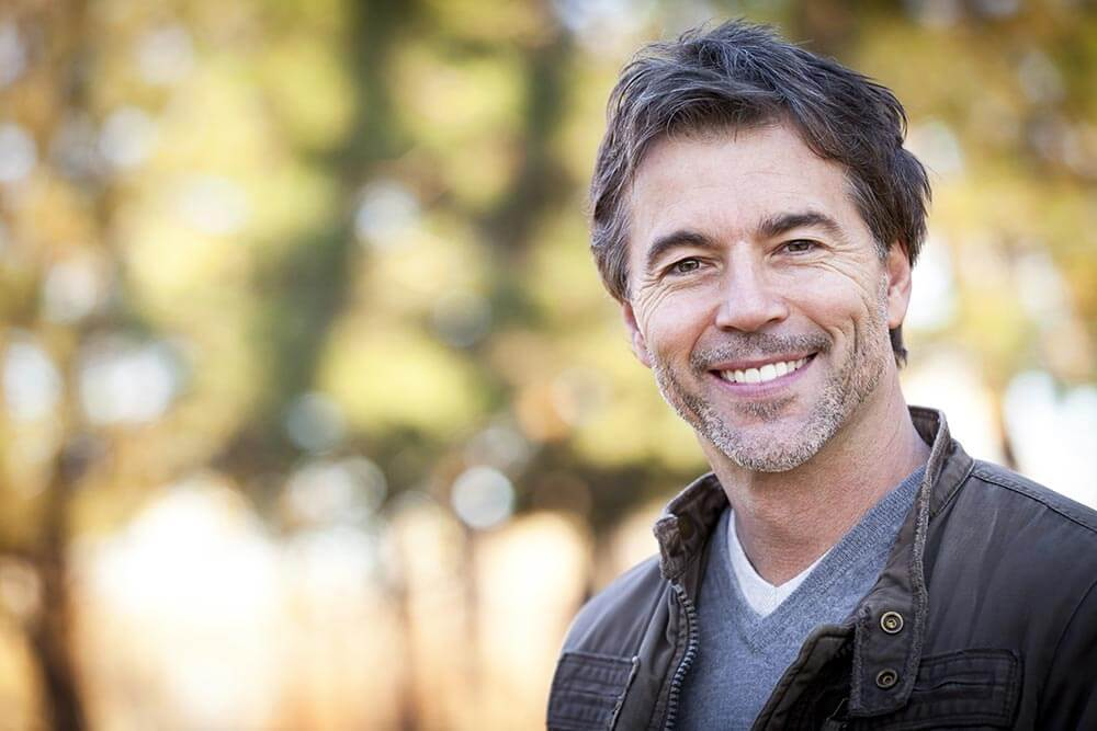 lighthousetreatment-have-i-hit-my-rock-bottom-article-photo-handsome-mature-happy-man-smiling-at-the-camera-outside-551276167