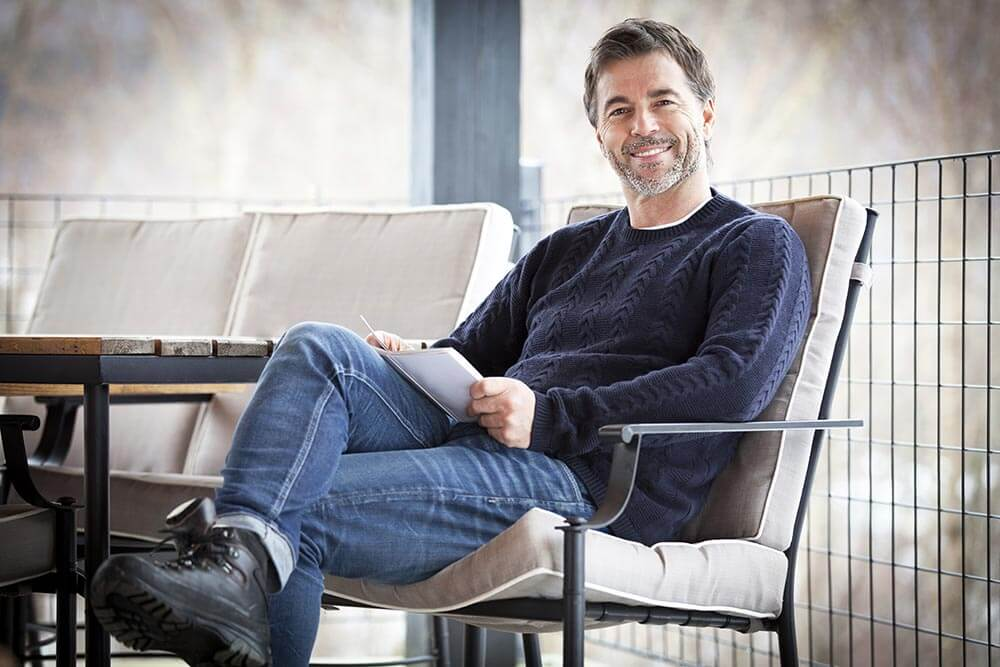 lighthousetreatment-six-ways-sobriety-changed-perception-world-article-photo-handsome-mature-happy-man-smiling-at-the-camera-outside-reading-a-book-640432084