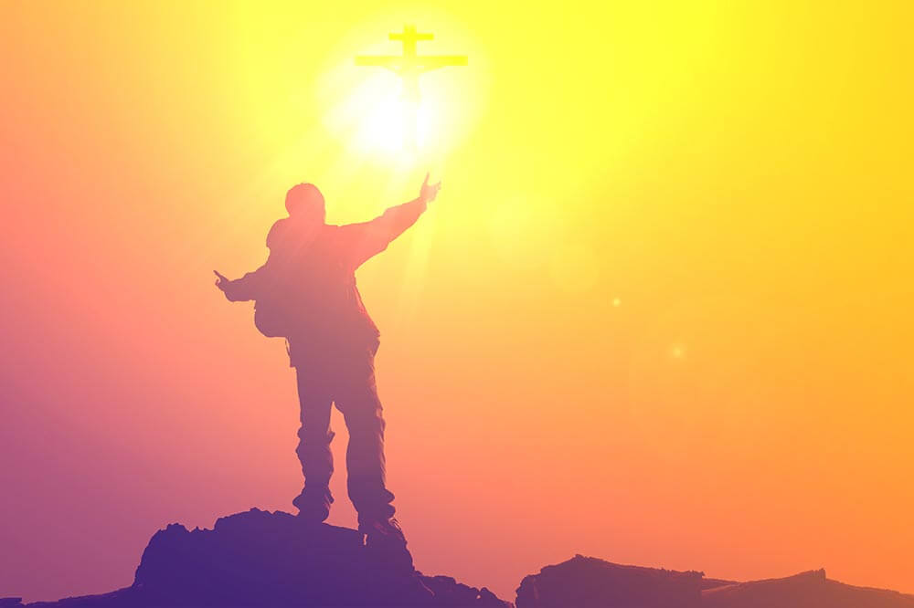 lighthousetreatment-six-ways-sobriety-changed-perception-world-article-photo-silhouette-of-man-praying-at-the-top-mountain-with-abstract-sun-cross-ray-god-power-547404493