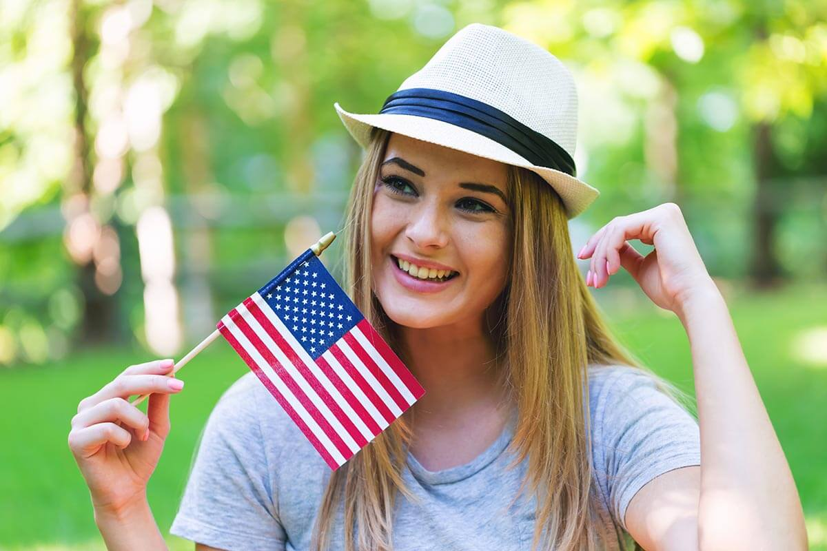 lighthousetreatment-7-ways-to-stay-sober-over-the-4th-of-july-article-photo-girl-with-an-american-flag-on-the-fourth-of-july-in-her-backyard-658705300
