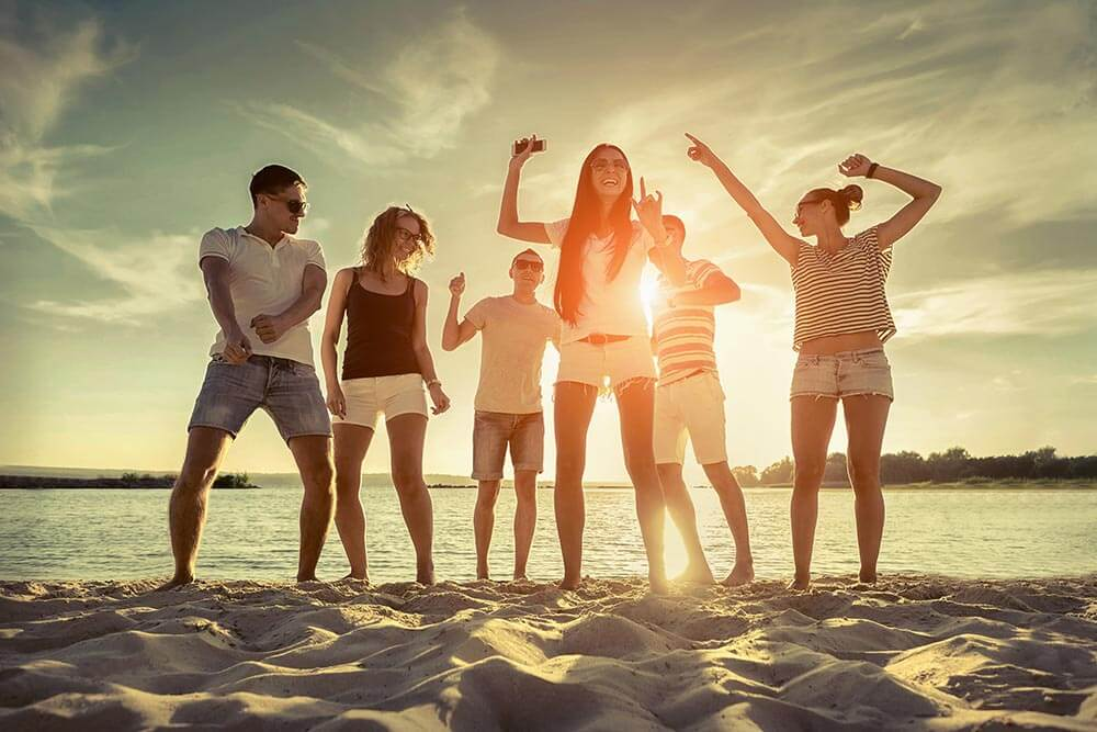 lighthousetreatment-what-do-i-do-all-summer-now-that-im-sober-article-photo-friends-funny-dance-on-the-beach-under-sunset-sunlight-437151931