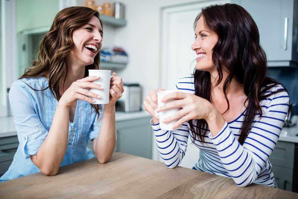 lighthousetreatment-7-tips-for-staying-positive-in-recovery-article-photo-happy-female-friends-holding-coffee-mugs-while-discussing-at-table-in-kitchen-411136360