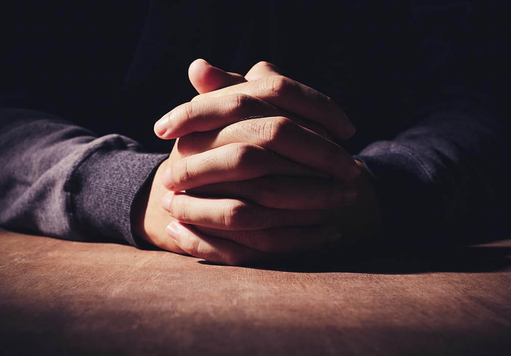 lighthousetreatment-the-complete-history-of-the-serenity-prayer-article-photo-praying-hands-of-young-man-on-a-wooden-desk-background-324611909
