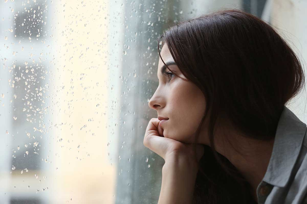 lighthousetreatment-how-secrets-in-recovery-keep-you-sick-article-photo-depressed-young-woman-near-window-at-home-closeup-606121190