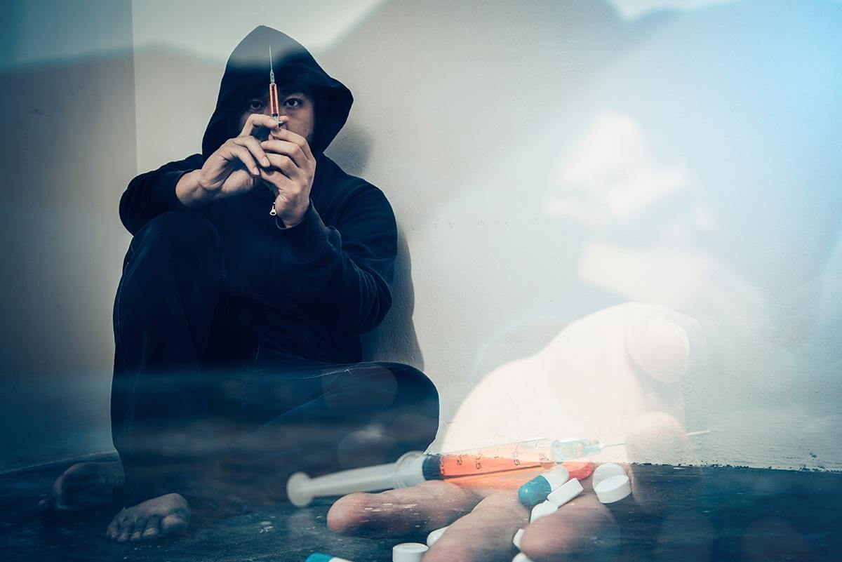 lighthousetreatment-the-suboxone-controversy-article-photo-double-exposure-overdose-asian-male-drug-addict-narcotic-syringe-on-hand-519236902