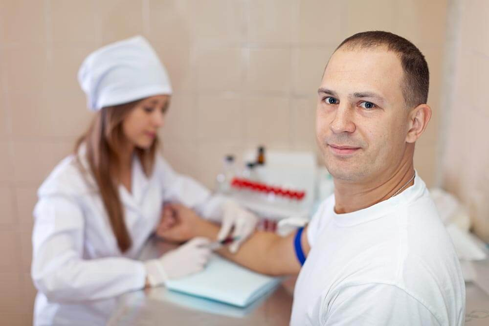man looking at camera while a nurse draws blood during a test for opiates