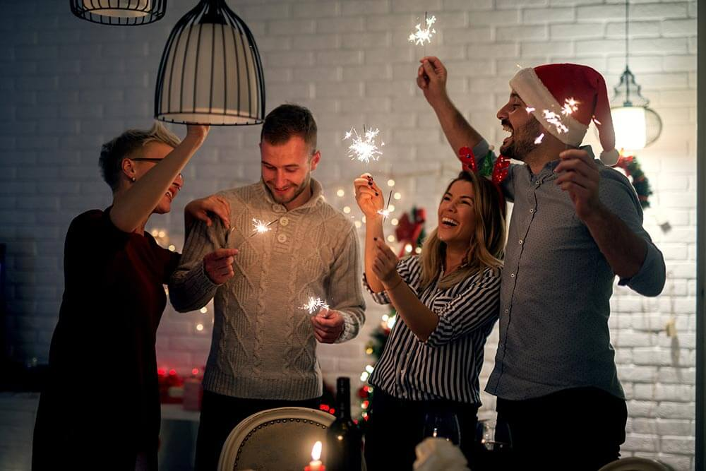 lighthousetreatment-how-to-stay-sober-and-have-fun-over-the-holidays-article-photo-group-of-smiling-friend-having-fun-with-sparkles-at-home-for-christmas-in-the-night-739355989