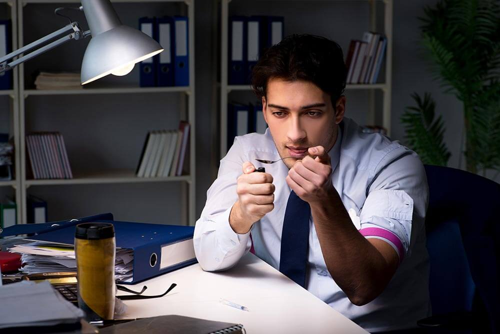 lighthousetreatment-the-relation-between-iq-and-drug-addiction-article-photo-employee-relieving-stress-from-overtime-with-drugs-narcotics-1064371199