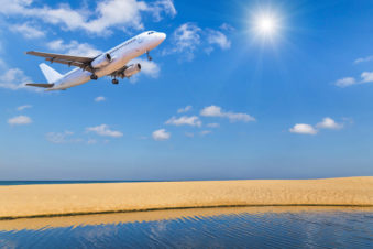 lighthouse-treatment-image-of-plane-landing-over-beach-541135675