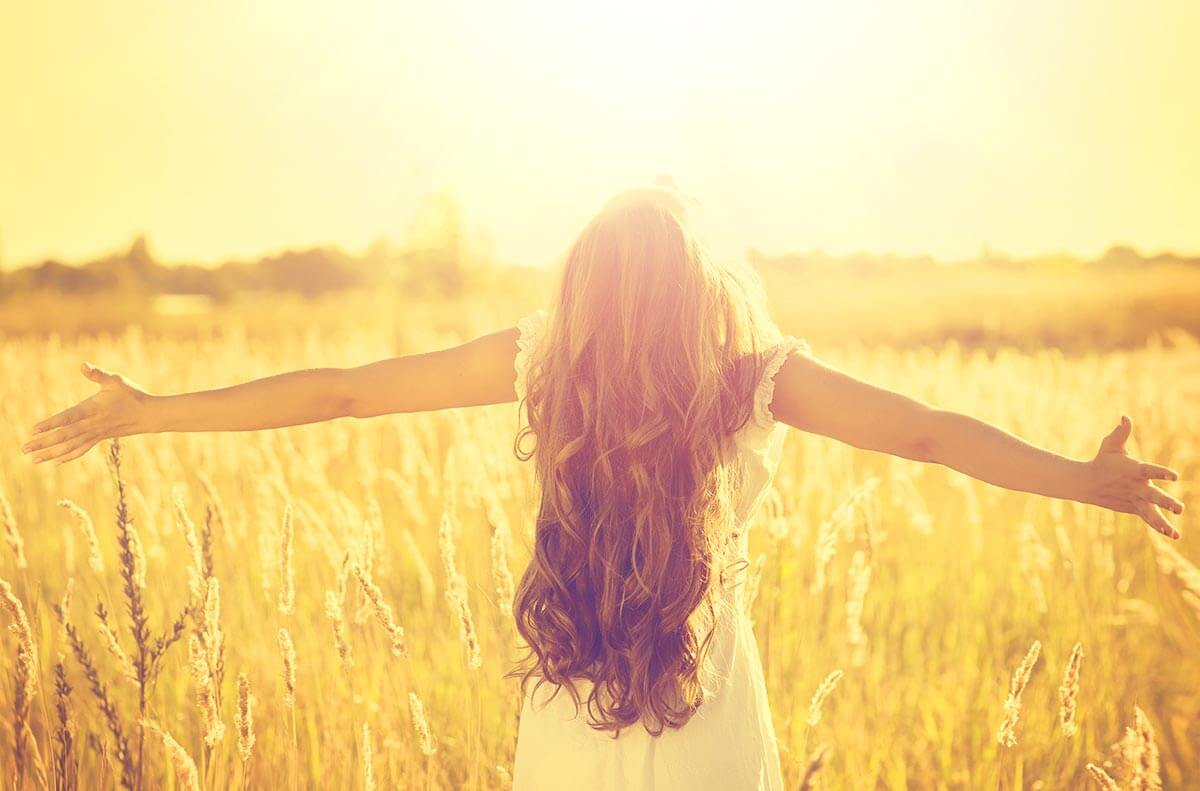 lighthousetreatment-what-is-a-spiritual-awakening-in-recovery-article-photo-autumn-girl-enjoying-nature-on-the-field-beauty-girl-outdoors-raising-hands-in-sunlight-rays