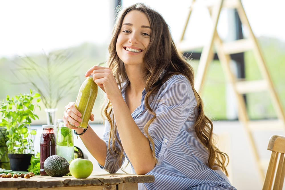 lighthousetreatment-8-tips-make-it-through-first-days-clean-and-sober-article-photo-beautiful-happy-woman-sitting-with-drinks-and-healthy-green-food-at-home-vegan-meal-and-detox