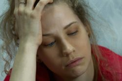 female opioid addict with hand on her head looking very sad