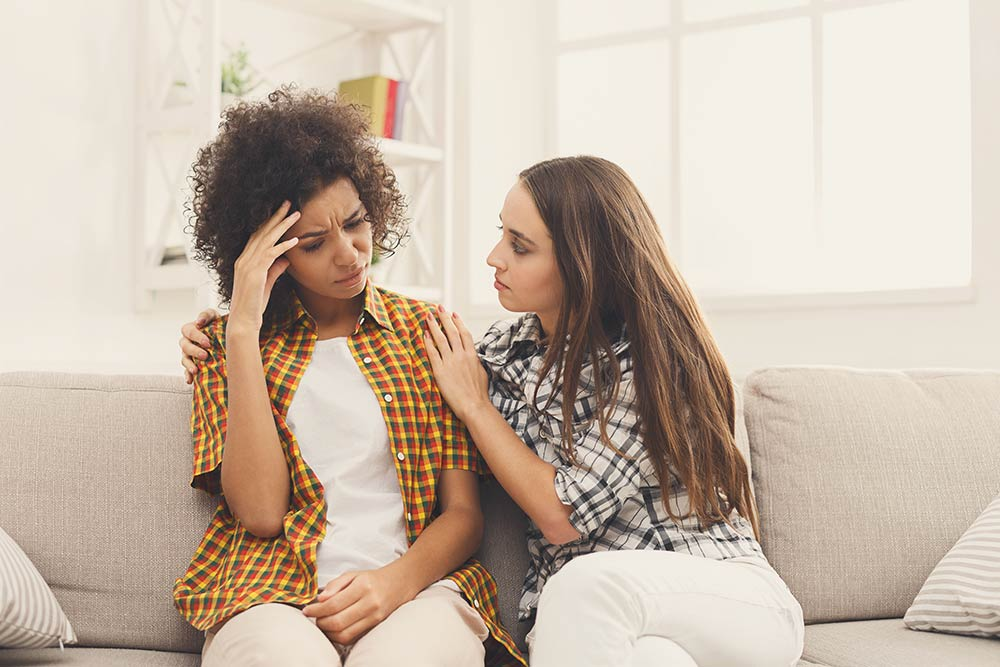 lighthousetreatment-8-tips-for-dealing-with-grief-and-loss-in-recovery-article-photo-two-sad-diverse-women-talking-at-home