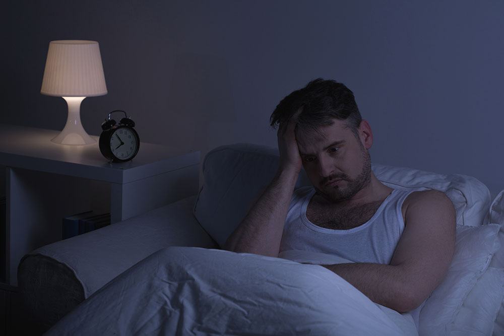 lighthousetreatment-what-is-ketamine-article-photo-man-suffering-from-sleeplessness-sitting-in-the-bed